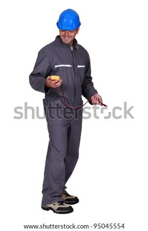 A tradesman holding a multimeter - stock photo