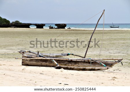 A traditional African dugout or dhow lies on the sands of a rural beach. - stock photo