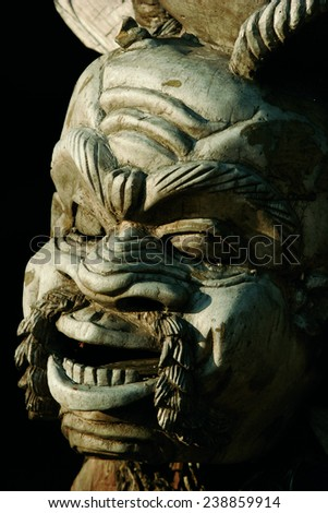 A traditional African wooden carving of a man's face. - stock photo