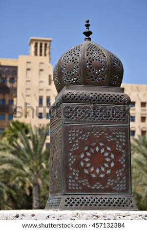 A traditional Arabian lantern or lamp against an Arabic backdrop. - stock photo