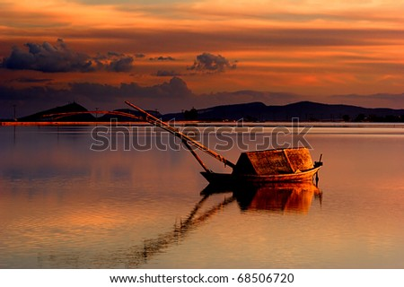 "A traditional boat of the lakes (called ""gaita"" in greek) in the lagoon of Messolonghi, around sunset - stock photo"