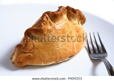 A traditional British Cornish Pasty - a pastry case filled with a thick meat and potato stew - with a fork on a plate.