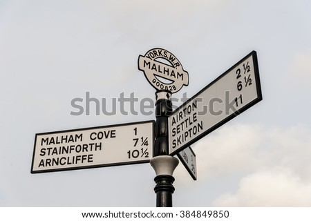 A traditional cast iron road direction sign in Malham, Yorkshire, England. - stock photo