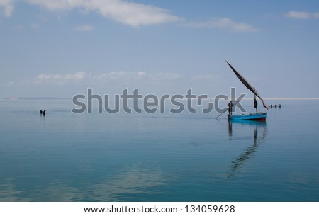A traditional dhow floats in the lagoons of the Bazaruto Archipelago in Mozambique where the fishermen fish in the shallows. - stock photo