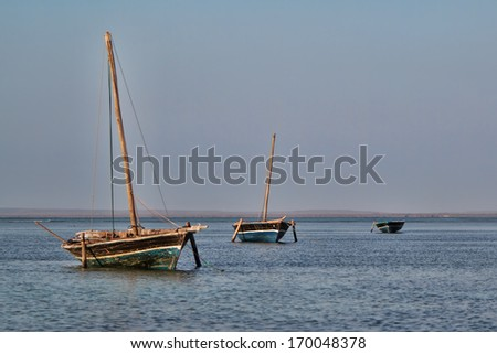 A traditional dhow or tribal sailing boat is anchored in the bay of Pemba in Northern Mozambique - stock photo