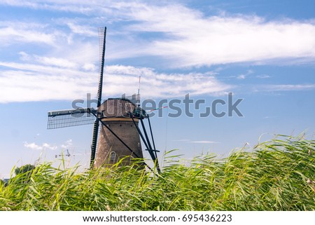 A traditional Dutch windmill against a blue sky at Kinderdijk, Netherlands