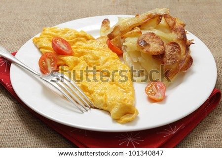 A traditional French omelet served with potatoes Anna - thinly sliced buttered potatoes baked in the oven - and garnished the miniature tomatoes