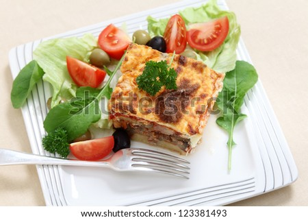 A traditional Greek moussaka , made with layers of potato, aubergine, meat, and tomato sauce, topped with bechamel sauce and served with salad. Viewed from above