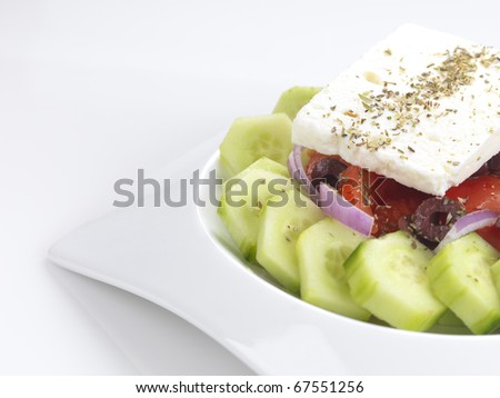 a traditional greek salad with feta cheese,tomatoes,cucumber,onion slices,olive slices,oregano and virgin olive oil