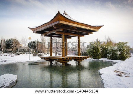 A traditional japanese temple in a lake with snow - stock photo