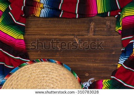 A traditional Mexican Sombrero and serape blanket on a wooden background with copy space - stock photo