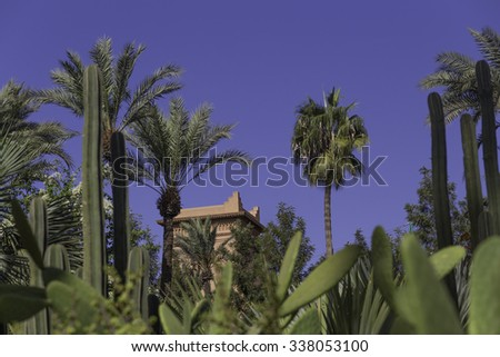 A traditional moroccan house or casbah surrounded by palm trees and cacti under a deep blue sky. - stock photo