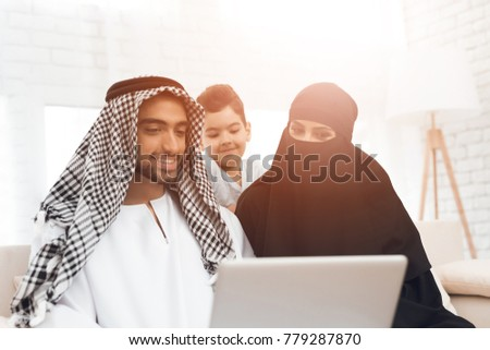 A traditional muslim family at home looks at the laptop screen. On the couch sat mother, father and little boy. The boy's mother wears a parandja.