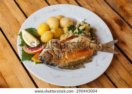 A traditional plate of grilled fish and sides in Croatian restaurant