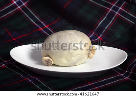 A traditional raw Scottish haggis, in a real sheep's stomach, on a plate with a tartan background