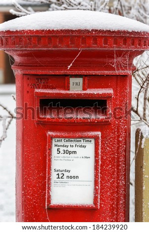 A Traditional Red English Post Box photographed after a winter snow storm. - stock photo