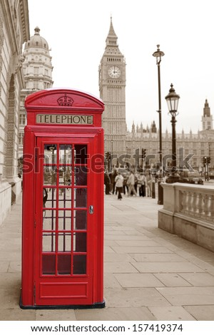 A traditional red phone booth in London with the Big Ben in a sepia background, short focus, background is blurred. - stock photo