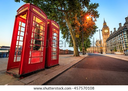 A traditional red phone booth in London with the Big Ben in the background. - stock photo