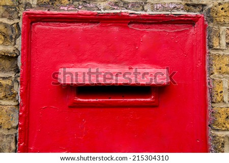 a traditional red post box in a wall.  - stock photo