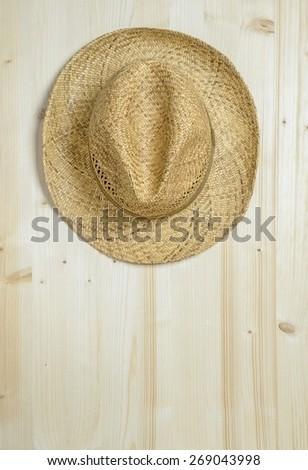 A traditional summer straw hat hanging on a wooden wall with copy space for your text - stock photo