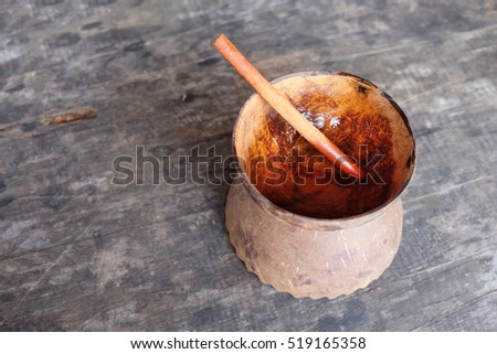 A traditional tea cup made from coconut shell with a cinnamon used as stirrer on a wooden grudge table.