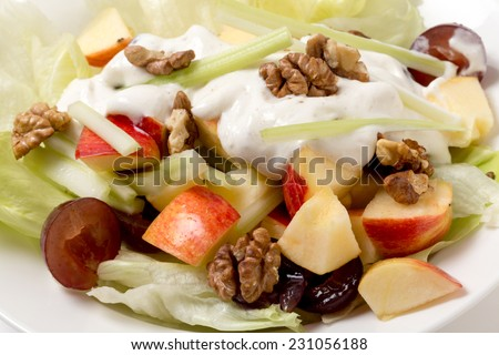 A traditional Waldorf Salad with lettuce, apple,grapes,walnuts,and celery sticks, topped with a modern dressing of yoghurt with cream, salt, pepper and walnut oil. - stock photo