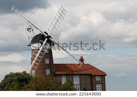 A Traditional Windmill Adjacent to a Brick House. - stock photo