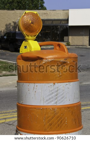 A traffic barrel that has been hit and beat up. - stock photo