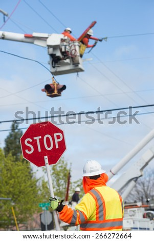 A traffic guard holds a stop sign as two power line technicians hover in the sky, repairing an electric line. - stock photo