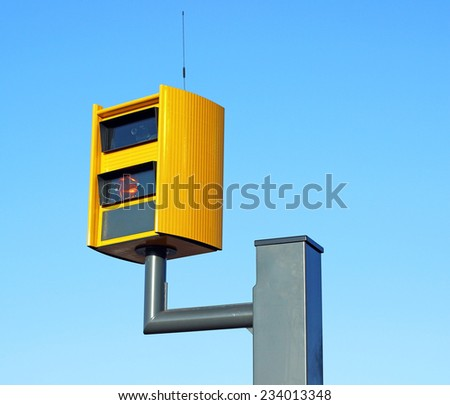 A traffic speed monitoring camera, against a bright blue sky.
