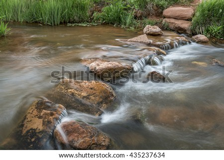 a trail crossing mountain creek with a row of step stones - Red Mountain Open Space, Colorado - stock photo