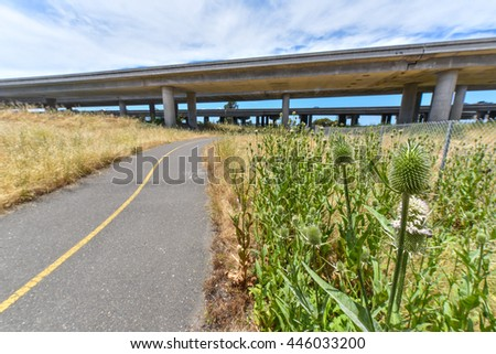 A trail for walking next to a freeway with fence. - stock photo