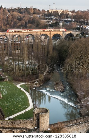 A train pass by the bridge at dusk, in luxembourg city - stock photo