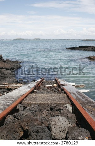 A train track runs from a boat shed into the water of the Hauraki Gulf