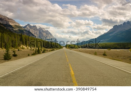 A tranquil and scenic drive through the heart of Banff, Alberta with mountains everywhere
