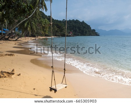 A tranquil beach scene at AoTan Khu near Trat in east Thailand. A wooden swing, palm trees and blue ocean make for a tropical paradise.
