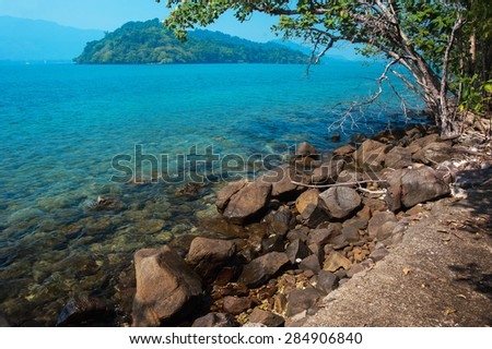 A tranquil seascape of marine sea with waves on stones and green island at background.