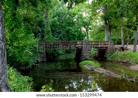 A Tranquil Spring or Summer Wooded Nature Outdoor Scene.  With bridge over creek.