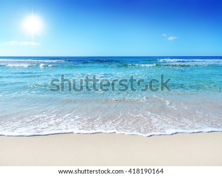 A tranquil sun and sea scene with starfish. The gently rolling waves of the sea roll in and out. - stock photo