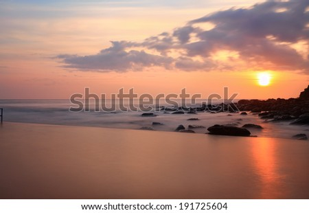 A tranquil view over the pool to the ocean at sunrise, NSW, Australia.  Long exposure - stock photo