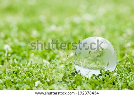 A transparent ball sitting in some short green grass. - stock photo
