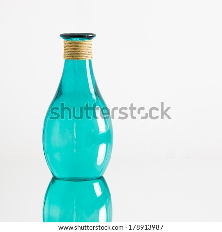 A transparent blue-green glass vase or bottle, with reflection, on white background