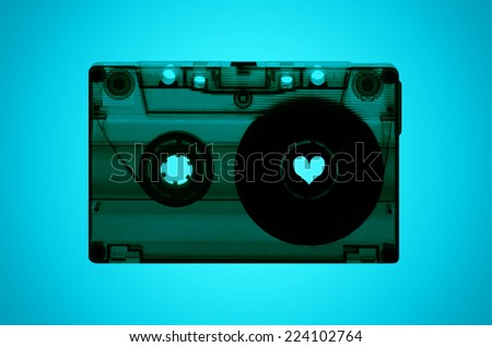 A transparent cassette tape on a light blue back-lit background with a heart shaped spool on the right hand side