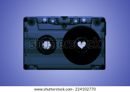 A transparent cassette tape on a purple back-lit background with a heart shaped spool on the right hand side