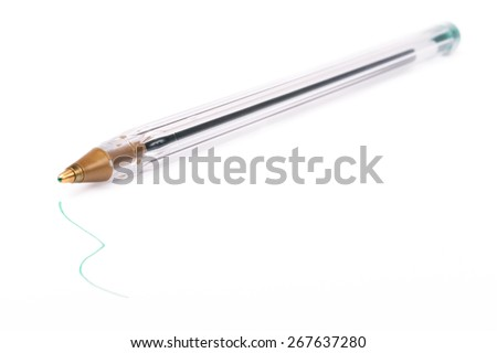 A transparent plastic ball pen on white background with smal drawing in the foreground. - stock photo