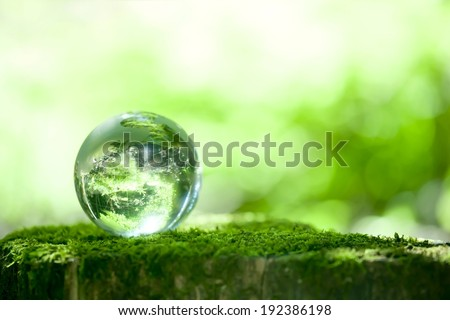 A transparent round bubble with green trees around. - stock photo