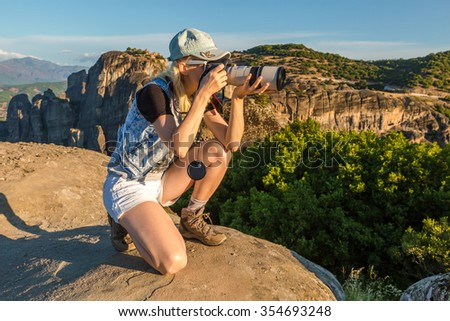 A travel photographer takes pictures of the spectacular monasteries of Meteora, Central Greece. Panoramic view from the best existing view point, a rock called Psaropetra. - stock photo