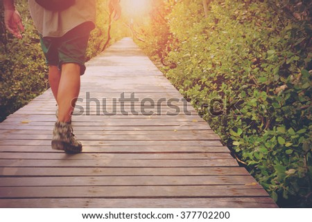 A traveler man walk along the wooden bridge surrounding with mangrove in the morning. Image make vintage tone - stock photo