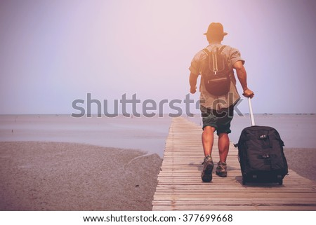A traveler man walk along the wooden bridge with his baggage. Image make vintage tone. - stock photo