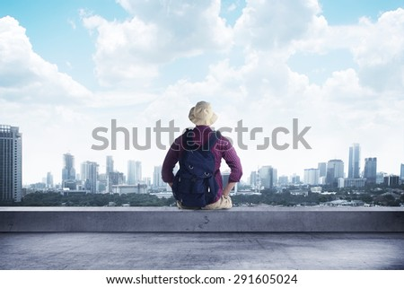 A traveler sitting on the rooftop watching at the city - stock photo